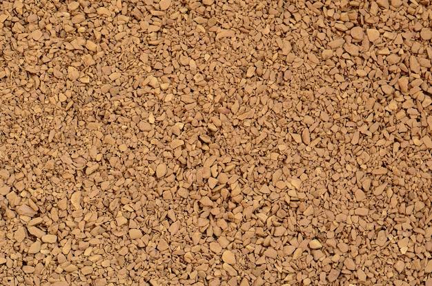 ダークブラウン色の多くの小さな小石の形で挽いたコーヒーの質感
