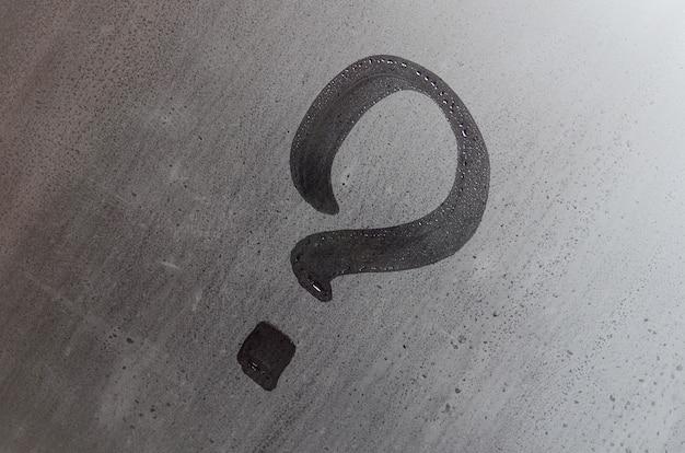 ガラス、疑問符の概念上の碑文。ミストや濡れた窓の表面に質問記号が描かれています