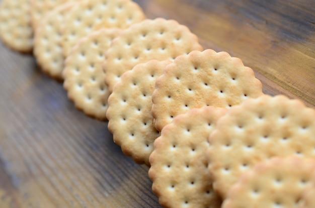 Круглое сэндвич-печенье с кокосовой начинкой в больших количествах лежит на коричневой деревянной поверхности.