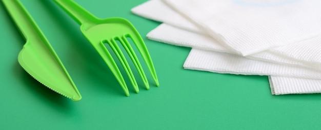 使い捨てのプラスチック製カトラリーグリーン。プラスチック製のフォークとナイフはナプキンの横にある緑の背景表面にあります。