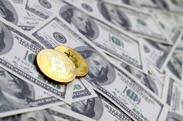Золотые биткойны лежат на множестве долларовых купюр. концепция поднятия цены биткойна относительно доллара сша