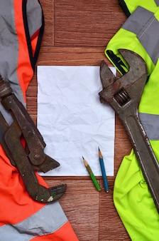 Мятый лист бумаги с двумя карандашами, окруженный зеленой и оранжевой рабочей униформой и разводными ключами