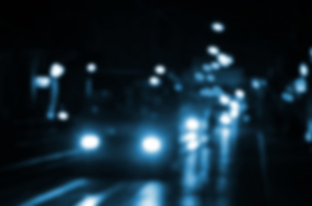 道路上のトラフィックの夜景がぼやけています。明るいヘッドライトで走行する車の多重像。