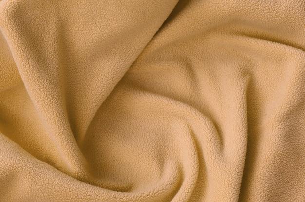 毛皮のようなオレンジ色のフリース生地の毛布。多くのレリーフフォールドを持つライトオレンジの柔らかい豪華なフリース素材