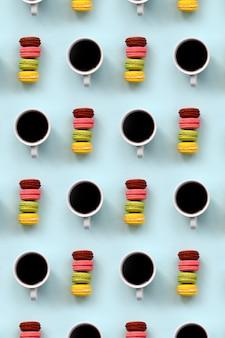 トレンディなパステルブルーの背景の平面図に多くのカラフルなデザートケーキのマカロンとコーヒーカップのパターン。フラットレイ構成