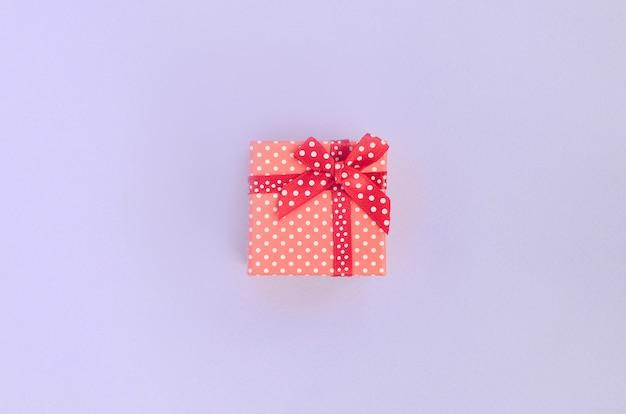 リボン付きの小さな赤いギフトボックスは紫色の背景にあります。