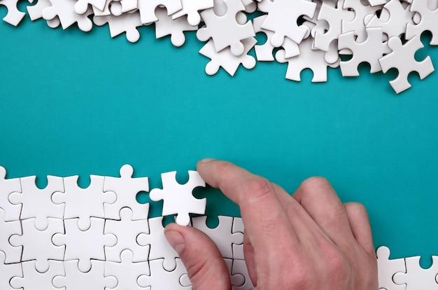 手が白いジグソーパズルを折ると裸のパズルのピースの山が青い表面の背景にあります。