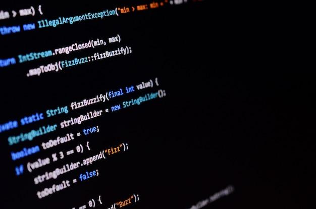 オフィスコンピューターのモニター上のコマンドラインのマクロ撮影。プログラマーの仕事の概念情報ラインの流れ