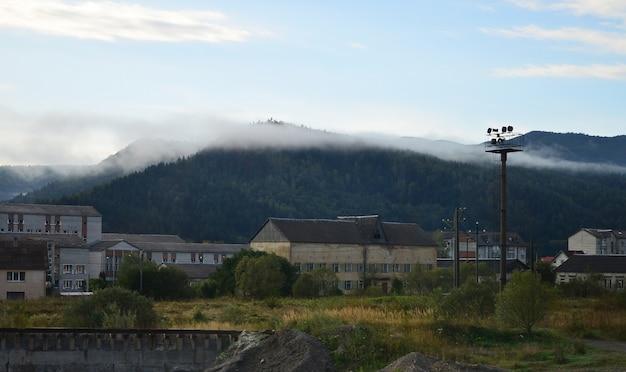 アパートの建物は霧の厚い層の前にあります。ウクライナのカルパティア山脈の山岳地帯に住んでいる