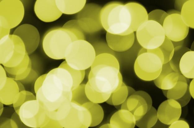 ピンぼけ効果ゴールデンイエローデフォーカス明るい背景。クリスマスライトのコンセプト