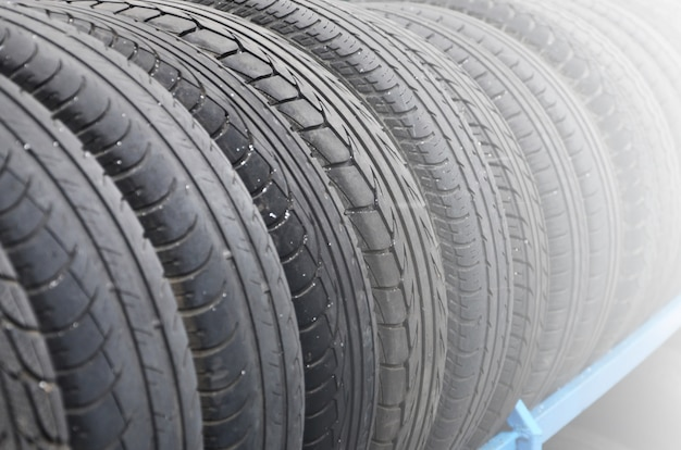自動車店でいろいろな車のタイヤを持っていく。多くの黒いタイヤ。タイヤスタックの背景。セレクティブフォーカス