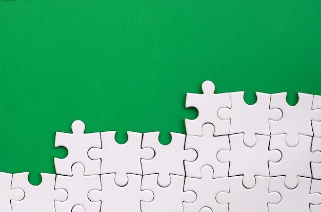 緑のプラスチック表面の背景に折り畳まれた白いジグソーパズルのフラグメント
