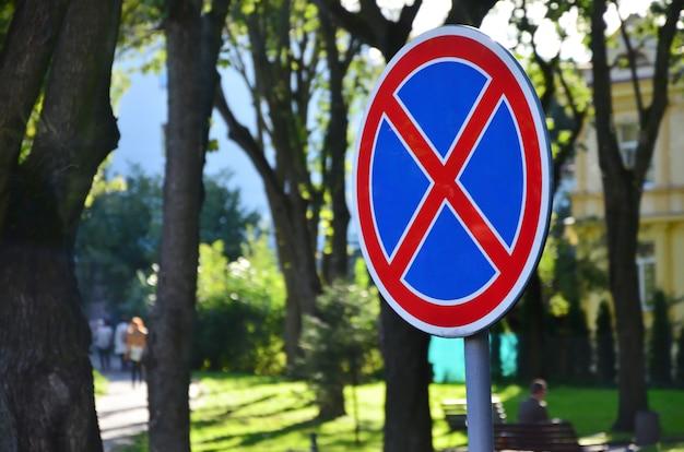 青色の背景に赤十字社と円形の道路標識。標識は駐車禁止を意味します