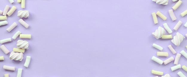 カラフルなマシュマロは紫色の紙の背景にレイアウトしました。パステルカラーのクリエイティブテクスチャフレームワーク。最小限の