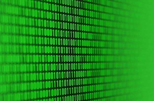 黒い背景に緑色の数字のセットで構成されたバイナリコードの画像
