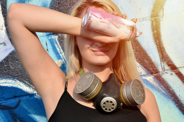 Молодая и красивая улыбающаяся граффити-художница с противогазом на шее, прикрывающая глаза аэрозольной баллончиком, стоящей на стене
