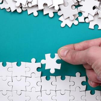 手は白いジグソーパズルを折り畳み、裸のパズルのピースの山は青い表面の背景にあります。