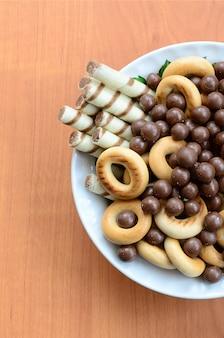 シャキッとした細管、チョコレートの溶けるボール、ベーグルは木製のテーブルの上の白いプレートにあります。様々なお菓子のミックス