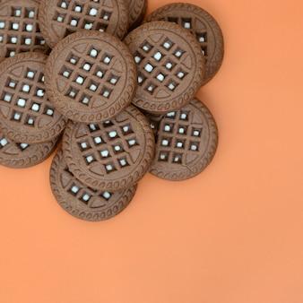 Детальное изображение темно-коричневого круглого сэндвич-печенья с кокосовой начинкой на оранжевой поверхности.