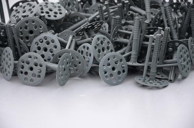 断熱用の多くの灰色のプラスチック製ダボの背景(固定)
