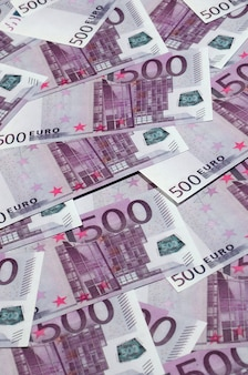 Денежный фон, состоящий из фиолетовых пятисот евро банкнот, разложенных по экрану