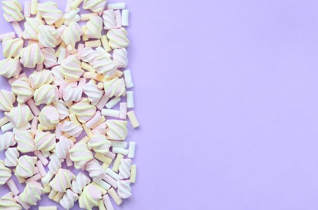 Красочный зефир выложил на фоне фиолетовый бумаги. пастельная креативная текстура. минимальный