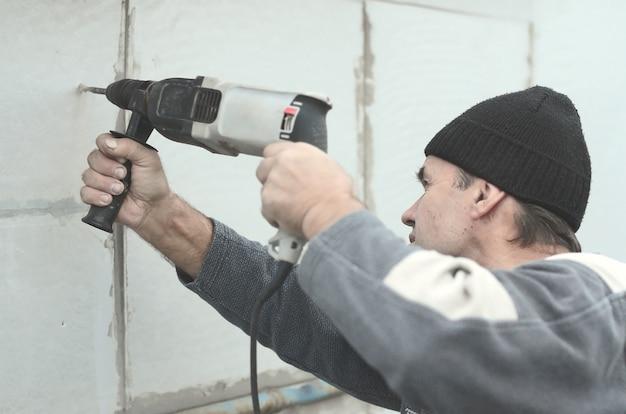 Пожилой рабочий сверлит отверстие в стене из пенопласта