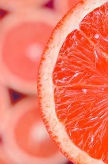 Вид сверху фрагмента ломтик красного грейпфрута на фоне