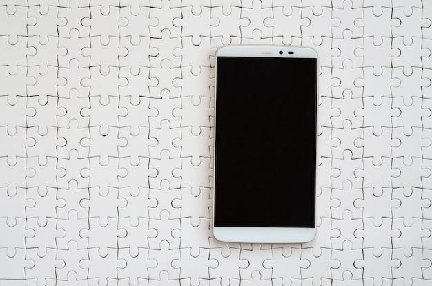 Современный большой смартфон с сенсорным экраном лежит на белой мозаике в собранном виде
