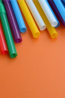 Много ярких соломинок для напитков лежит на ярко-оранжевом фоне поверхности