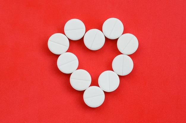 Несколько белых таблеток лежат на ярко-красном фоне