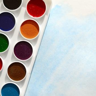 Новый набор акварели лежит на листе бумаги, на котором изображен абстрактный акварельный рисунок