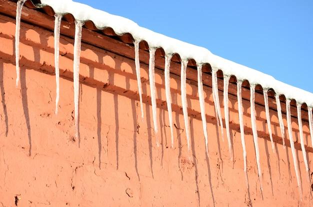 たくさんの長いつららが赤レンガの建物の屋根の下にぶら下がっています
