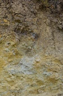 砂の採石場で固体黄色と茶色の砂の壁のテクスチャ
