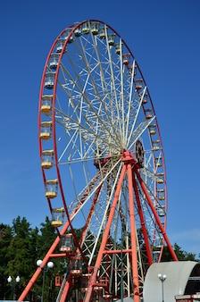 Большое и современное многоцветное колесо обозрения на фоне чистого голубого неба