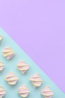Разноцветный зефир на фоне фиолетового и синего бумаги