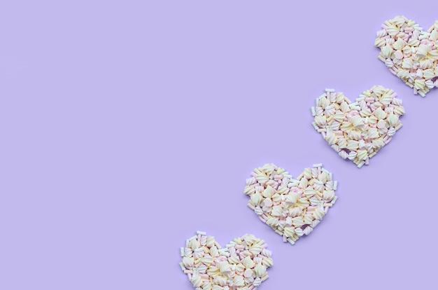 Разноцветный зефир на фиолетовом и розовом фоне