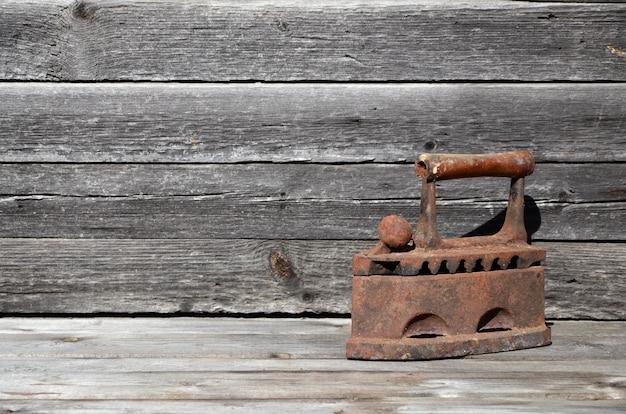 重くてさびた古い石炭鉄は木の表面にあります