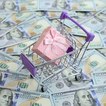 Подарочная коробка в маленькой корзинке лежит на многих долларовых купюрах