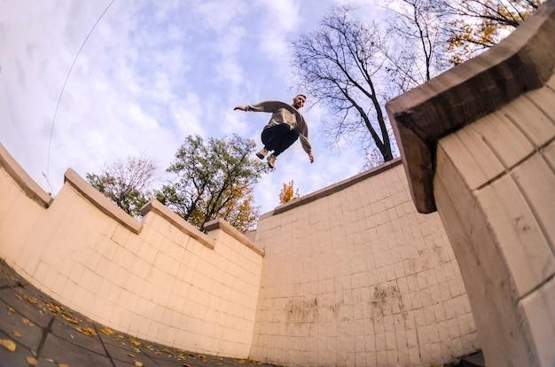 一人の若い男がコンクリートのパラペットの間の空間を飛び越えます。
