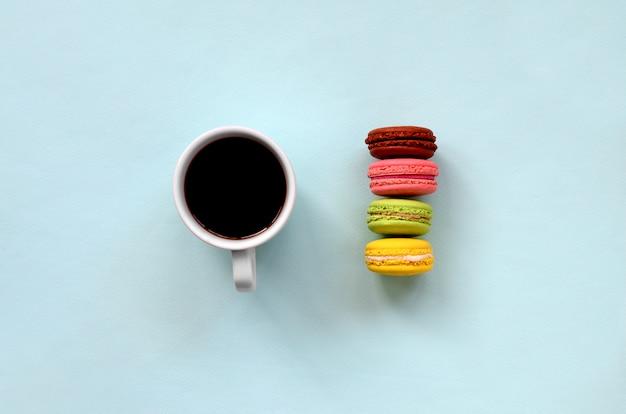 カラフルなデザートケーキマカロンまたはマカロンとトレンディなパステル調の青い背景の上のコーヒーカップ