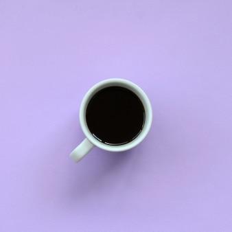 ファッションパステルバイオレットカラー紙のテクスチャ背景に小さな白いコーヒーカップ