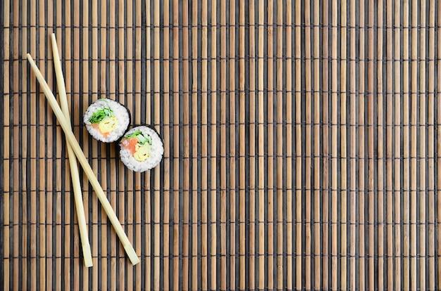 巻き寿司と木の箸は、竹のわらのサービングマットの上にあります。