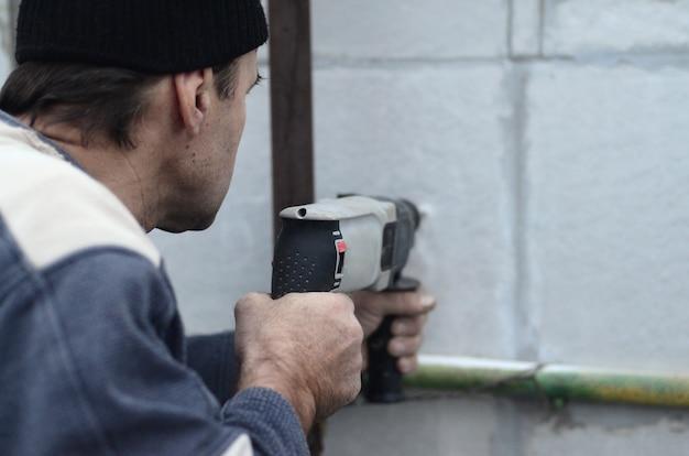Пожилой рабочий сверлит отверстие в стене из пенопласта для последующей установки