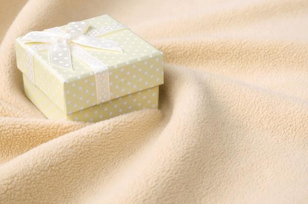 小さな弓とオレンジ色の小さなギフトボックスは、毛布の上にあります。