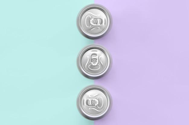 Металлические пивные банки на фоне текстуры модной пастельной бумаги фиолетового и синего цветов
