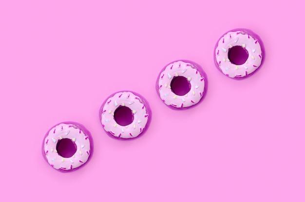 パステルカラーのカラフルな背景にある多くの小さなプラスチック製のドーナツ