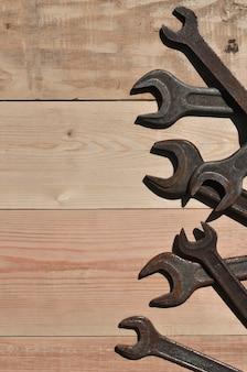 Несколько ржавых гаечных ключей лежит на деревянном столе в мастерской
