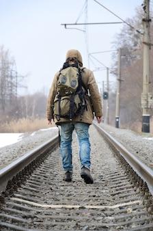 大きなバックパックを持った男が鉄道線路を走ります