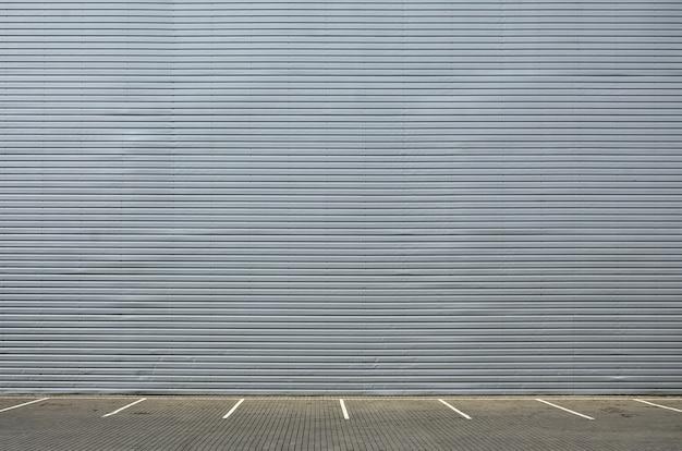 製品配置用のスペースを持つ金属製の壁の背景に空の駐車スペース